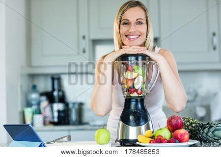 Pretty blonde woman preparing a smoothie in the kitchen