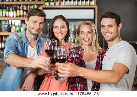 Friends toasting with wine at a bar