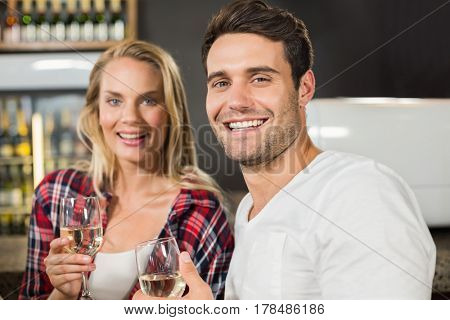 Couple looking at camera with glasses of white wine in hands