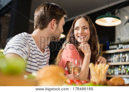Couple looking at each other at bar
