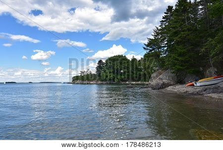 Kayak and row boat on the shore of a rocky beach in Casco Bay Maine.