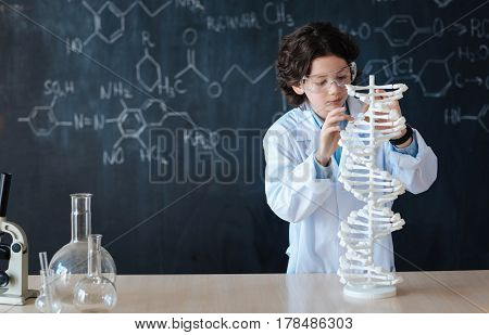 Taking part in the chemistry project. Intelligent involved diligent pupil standing near the blackboard at school while having lesson and taking part in the chemistry project