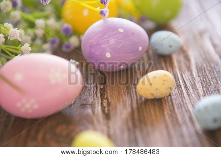 Easter Eggs And Branch With Flowers On Rustic Wooden Background.