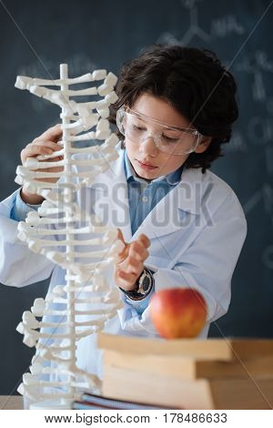 Gifted pupil researching science . Hardworking crafty diligent kid standing in front of the blackboard at school while studying science and working on the project