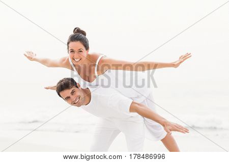 Man giving a piggy back to woman on the beach on a sunny day