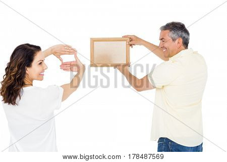 Happy couple holding picture frame against white background