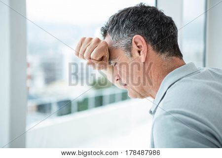 Tensed man leaning on glass window at home