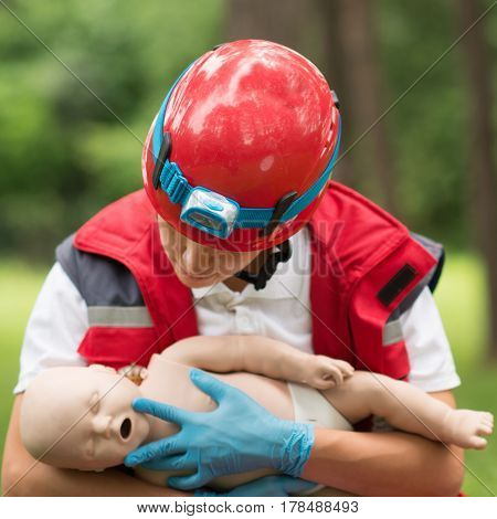 Cpr training on baby dummy outdoors, color image