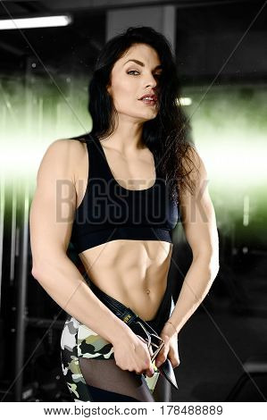 Handsome caucasian muscular girl on diet in the gym after execute exercise. Sexy woman powerful training arms pectorals and shoulders
