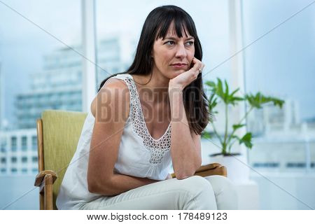 Pregnant woman sitting depressed at home