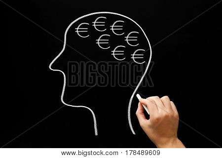 Hand drawing human head and many euro signs with white chalk on blackboard.
