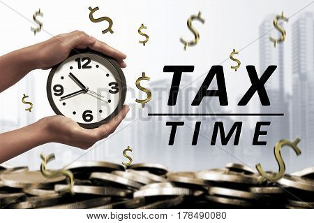 People Hand Holding Alarm Clock Beside Tax Time Message