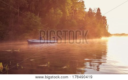 A young guy rides a boat on a lake during a golden sunset. Man rowing a boat in backlight of the sun. Unity with nature concept