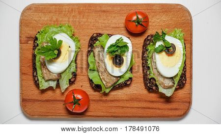 Sandwich on black bread with egg and sardines, sprats, lettuce and tomatoes. On the desk
