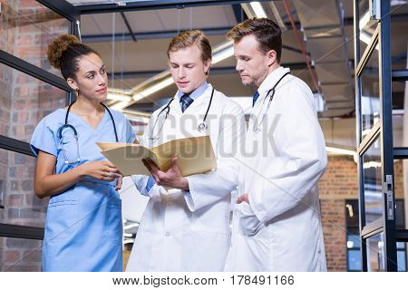 Doctors discussing a medical report in hospital