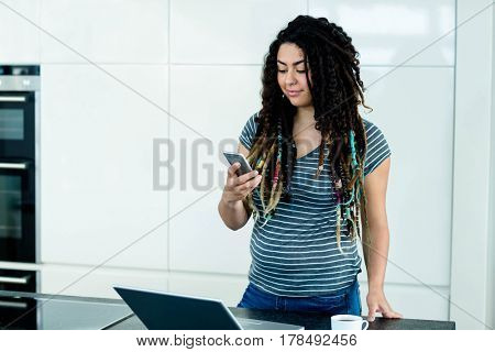 Woman standing near worktop and using a mobile phone and laptop