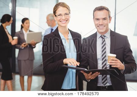 Portrait of businessman and businesswoman holding file in office