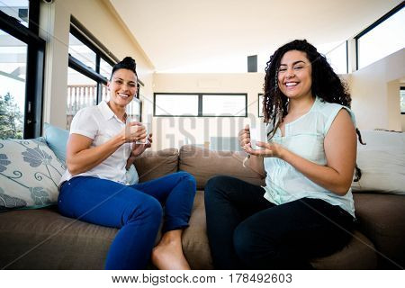 Portrait of lesbian couple smiling while having a cup of coffee