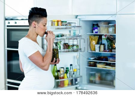 Pregnant woman standing near open refrigerator and eating pickles
