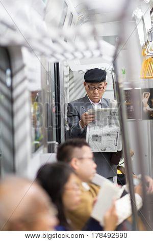Tokyo, Japan - November 6, 2015: Japanese businessman taking ride to work, standing inside public transport and reading newspaper on November 6th in Tokyo, Japan, 2015 .