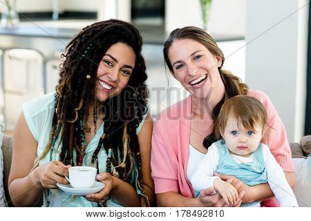 Portrait of two women smiling and sitting on sofa with a baby