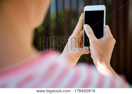 female hands, outside, typing on the screen of a smartphone