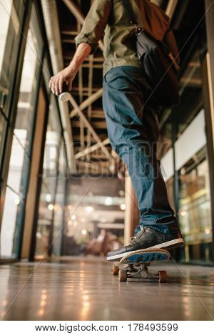 Rear view shot of man skateboarding in office corridor. Young businessman skating through his startup office.