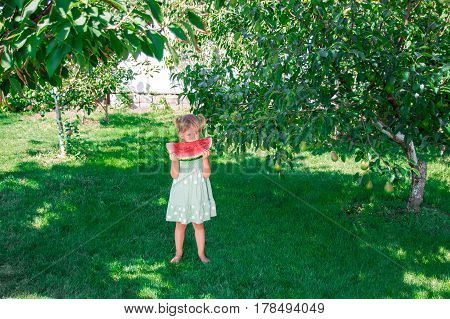 Little Girl In Green Dress, Barefoot Standing In The Park With Big Slice Watermelon. Summer. Outdoor