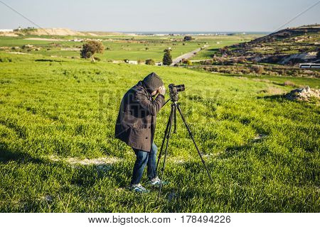 A photographer or traveller using a professional DSLR camera on a tripod in the nature for background