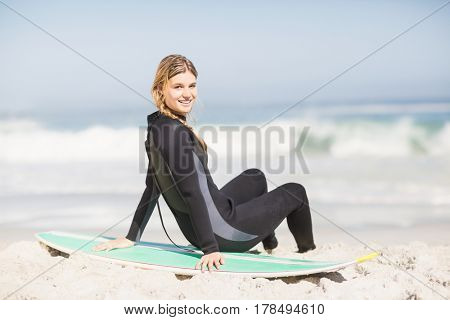 Portrait of woman in wetsuit sitting with surfboard on the beach on a sunny day