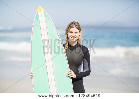 Portrait of woman in wetsuit holding a surfboard on the beach on a sunny day