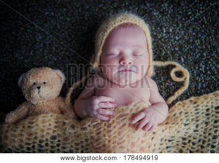 Newborn baby in a cap sleeping with a soft toy