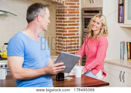 Happy husband using tablet while wife having breakfast in the kitchen