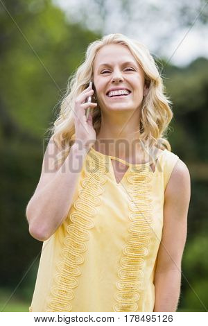 Happy woman making a phone call outside