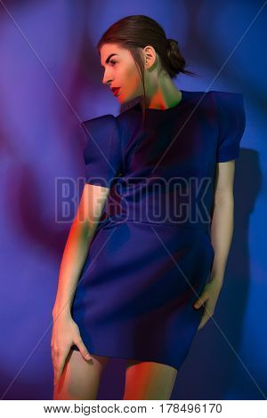Pretty fashionable woman looking away standing in the deep blue dress. Vertical studio shot.