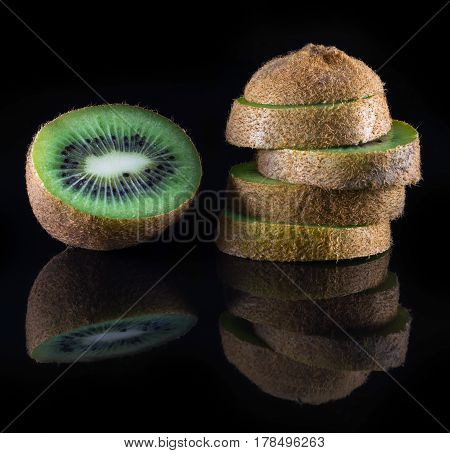 fresh kiwi on a black background with reflection closeup