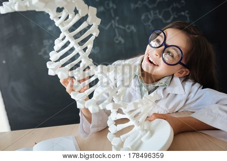 Hopeful young generation studying. Amused smart crafty child sitting in the lab and enjoying biology class while learning and exploring DNA model