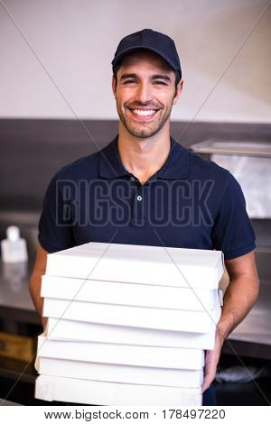 Pizza delivery man carrying boxes in commercial kitchen