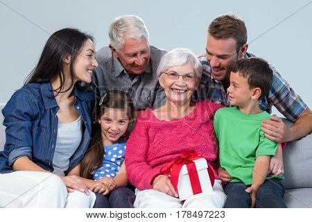 Family giving a gift to grandmother, sitting on sofa in living room