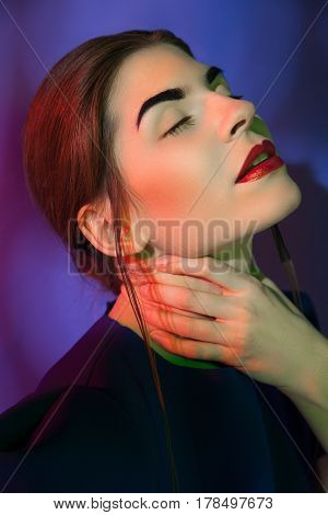 Pretty young woman looking away and holding her neck. Vertical studio shot.