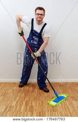 Man cleans the floor. He is smiling.