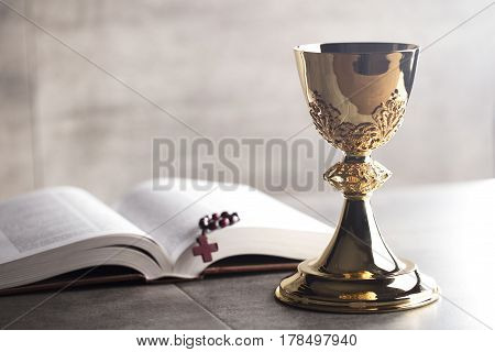 Catholic religion theme.  Holy Bible and gold chalice on glass table and stone background.