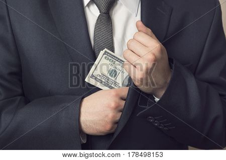 Detail of a man in a suit placing money in his jacket pocket. Selective focus