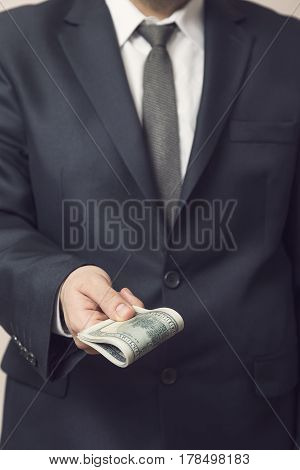 Detail of a business man offering a bribery money. Selective focus