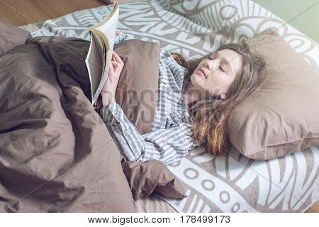 Cute Girl Reading A Book While Lying In Bed