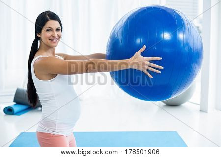 Portrait of pregnant woman exercising with exercise ball at home