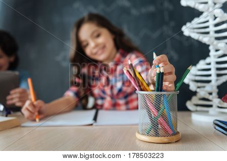 Full of creative ideas. Artistic talented gifted girl sitting at school and drawing while working on the project and using colorful pencils