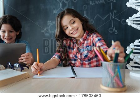 Full of lively emotions. Capable skilled cute girl sitting at school and enjoying art class while working on the project and using colorful pencils