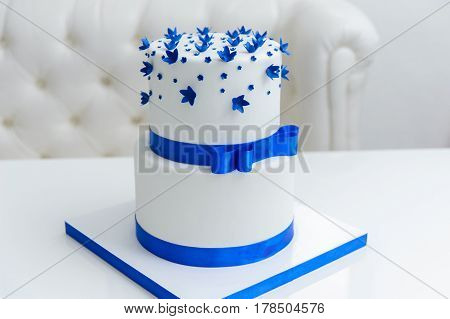 White wedding cake with blue flowers and a bow.