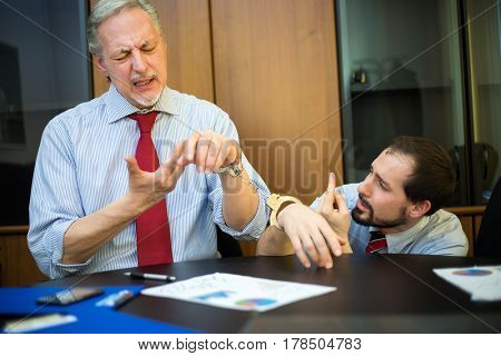 Business people in handcuffs